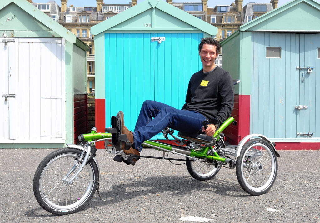 A white male with dark hair is sitting on a green recumbent trike, smiling towards the camera. Behind him is a birghtly b=coloured shed, blue and red.